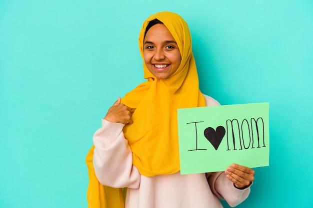 Junge kaukasische frau, die eine ich liebe mutter lokalisiert auf rosa hintergrundperson hält, die von hand auf einen hemdkopierraum zeigt, stolz und zuversichtlich