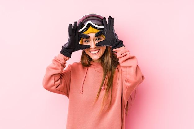 Junge kaukasische frau, die eine isolierte skikleidung trägt, die okay zeichen über augen zeigt