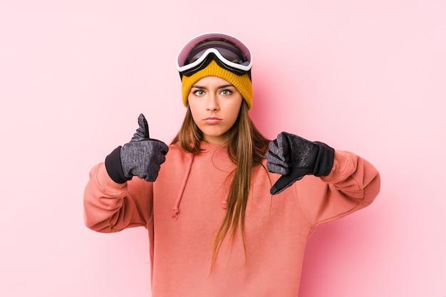 Junge kaukasische frau, die eine isolierte skikleidung trägt, zeigt daumen hoch und daumen runter, schwieriges auswahlkonzept