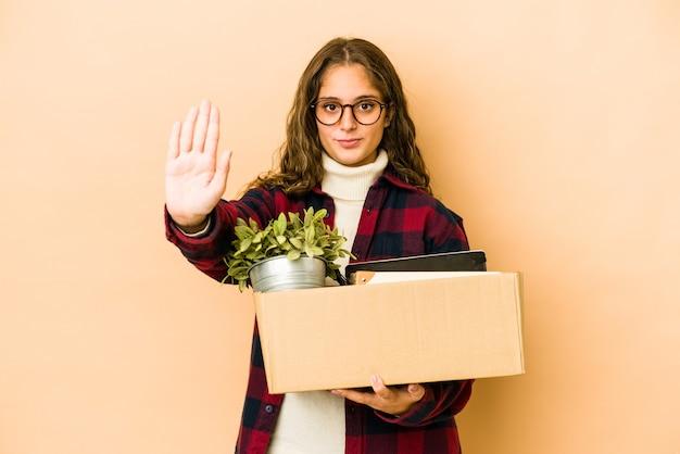 Junge kaukasische frau, die eine isolierte stehende box mit ausgestreckter hand hält, die stoppschild zeigt, das sie verhindert.