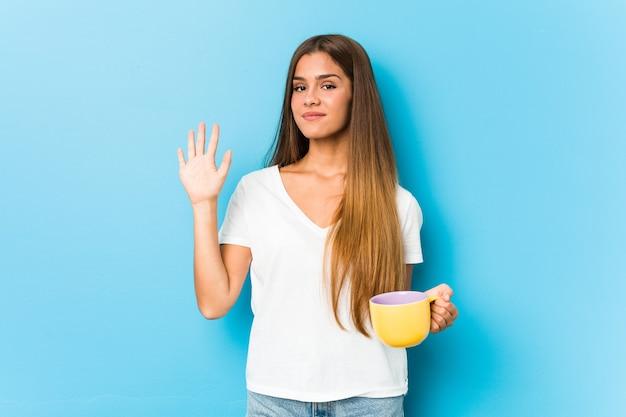 Junge kaukasische frau, die eine kaffeetasse hält, die fröhlich lächelnd zeigt nummer fünf mit den fingern.