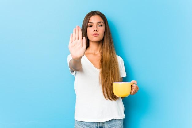 Junge kaukasische frau, die eine kaffeetasse hält, die mit ausgestreckter hand steht, die stoppschild zeigt, das sie verhindert.