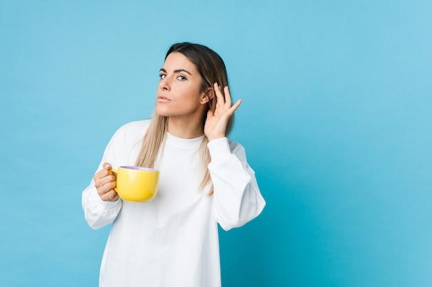 Junge kaukasische frau, die eine kaffeetasse hält, die versucht, einen klatsch zu hören.