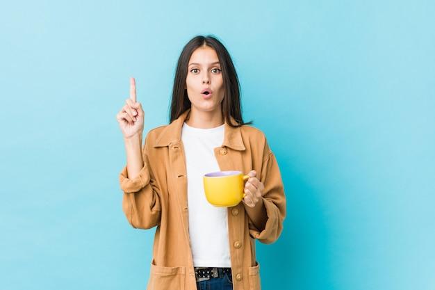 Junge kaukasische frau, die eine kaffeetasse hat irgendeine großartige idee, konzept der kreativität hält.