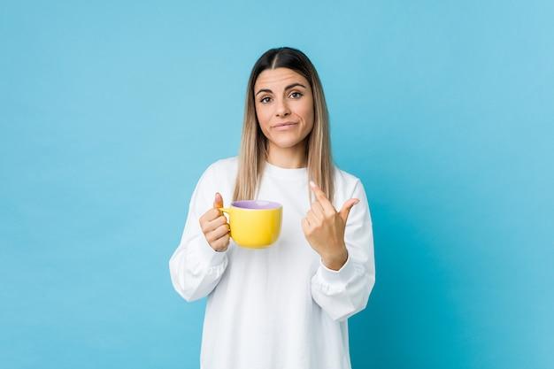 Junge kaukasische frau, die eine kaffeetasse zeigt mit dem finger auf sie hält, als ob einladung näher kommen.
