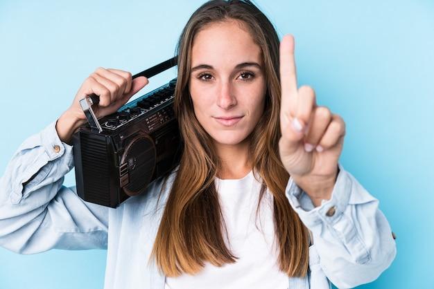 Junge kaukasische frau, die eine kassette lokalisiert zeigt nummer eins mit finger hält.