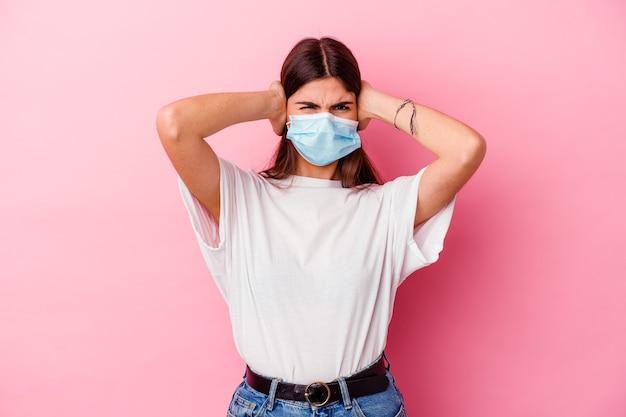 Junge kaukasische frau, die eine maske für virus auf rosa bedeckenden ohren mit händen trägt, die versuchen, nicht zu lauten ton zu hören.