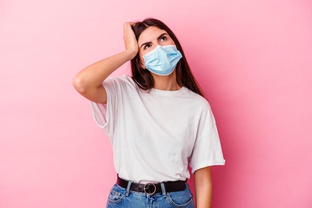 Junge kaukasische frau, die eine maske für virus isoliert auf rosa wand müde und sehr schläfrig hält hand auf kopf hält.