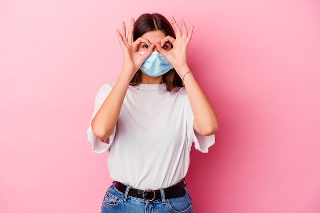 Junge kaukasische frau, die eine maske für virus lokalisiert auf rosa hintergrund trägt, der okay zeichen über augen zeigt