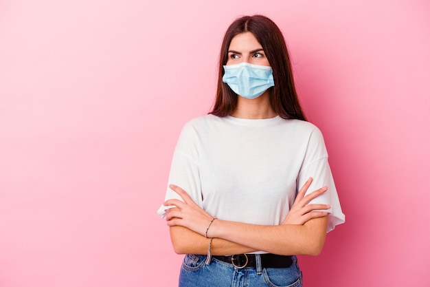 Junge kaukasische frau, die eine maske für virus lokalisiert auf rosa wand trägt, die zuversichtlich mit verschränkten armen lächelt.