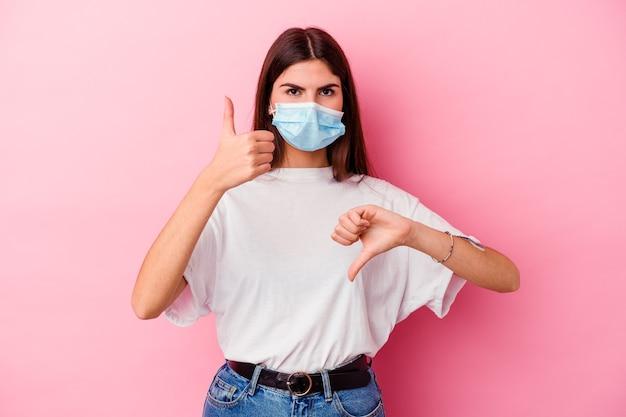 Junge kaukasische frau, die eine maske für virus trägt, isoliert auf rosa wand, die daumen oben und daumen unten zeigt, schwieriges konzept wählen