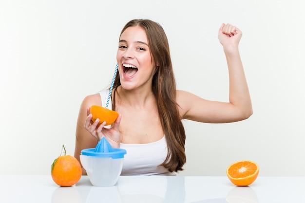 Junge kaukasische frau, die eine orange mit einem strohhalm trinkt. gesundes leben-konzept
