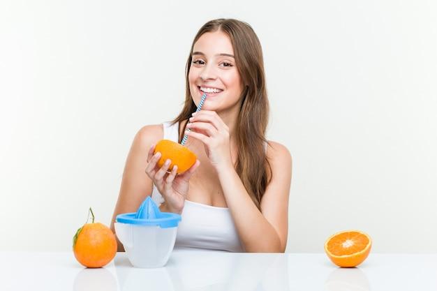 Junge kaukasische frau, die eine orange mit einem strohhalm trinkt.