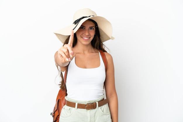 Junge kaukasische frau, die eine pamela in den sommerferien trägt, isoliert auf weißem hintergrund, die einen finger zeigt und hebt