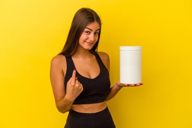 Junge kaukasische frau, die eine proteinflasche isoliert auf gelbem hintergrund hält und mit dem finger auf sie zeigt, als ob sie einladen würde, näher zu kommen