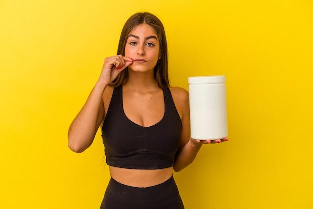 Junge kaukasische frau, die eine proteinflasche lokalisiert auf gelbem hintergrund mit den fingern auf den lippen hält, die ein geheimnis halten.