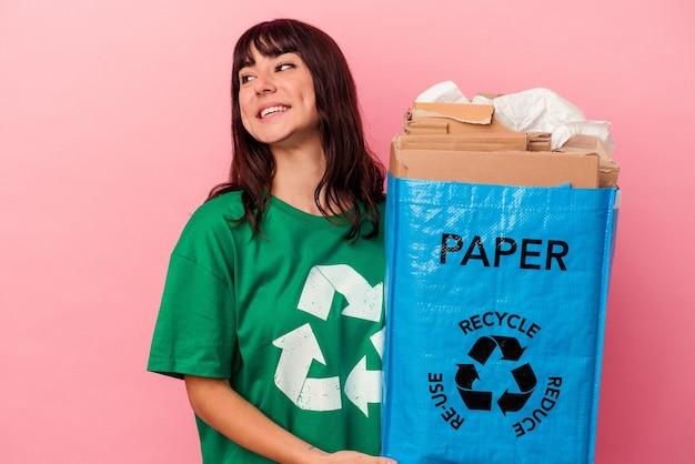 Junge kaukasische frau, die eine recycelte papptüte einzeln auf rosafarbenem hintergrund hält, sieht beiseite lächelnd, fröhlich und angenehm aus.