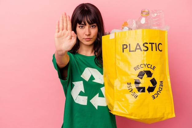 Junge kaukasische frau, die eine recycelte plastiktüte lokalisiert auf rosa hintergrund steht, steht mit ausgestreckter hand, die stoppschild zeigt, das sie verhindert.