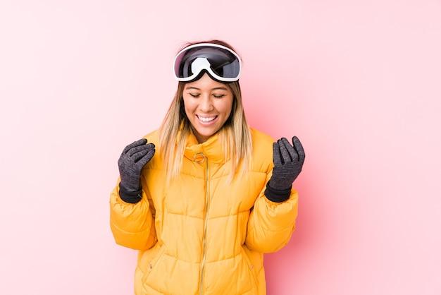 Junge kaukasische frau, die eine skikleidung in einem rosa hintergrund freudig lachend viel trägt. glückskonzept.