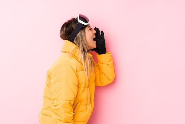 Junge kaukasische frau, die eine skikleidung in einem rosa hintergrund trägt, der handfläche nahe geöffnetem mund schreit und hält.
