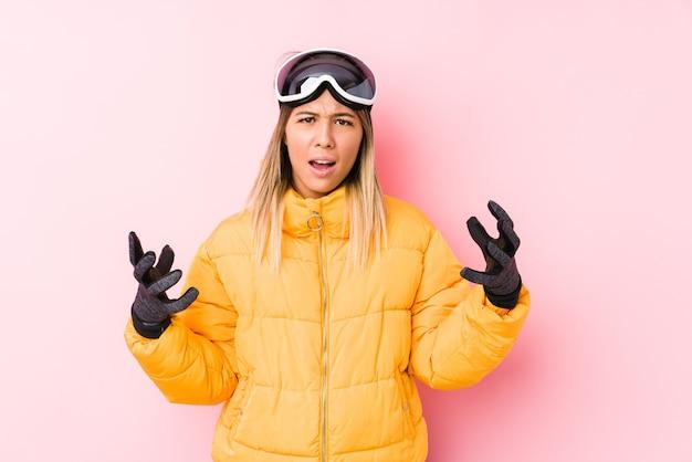 Junge kaukasische frau, die eine skikleidung in einem rosa hintergrund trägt, der mit wut schreit.