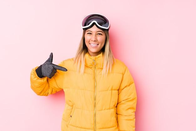 Junge kaukasische frau, die eine skikleidung in einer rosa hintergrundperson trägt, die von hand auf einen hemdkopierraum zeigt, stolz und zuversichtlich