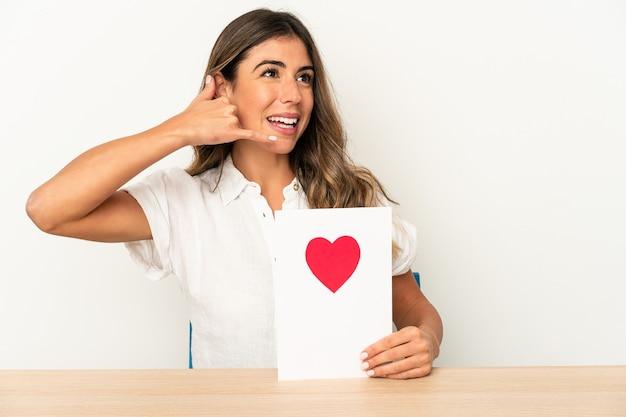 Junge kaukasische frau, die eine valentinstagkarte hält
