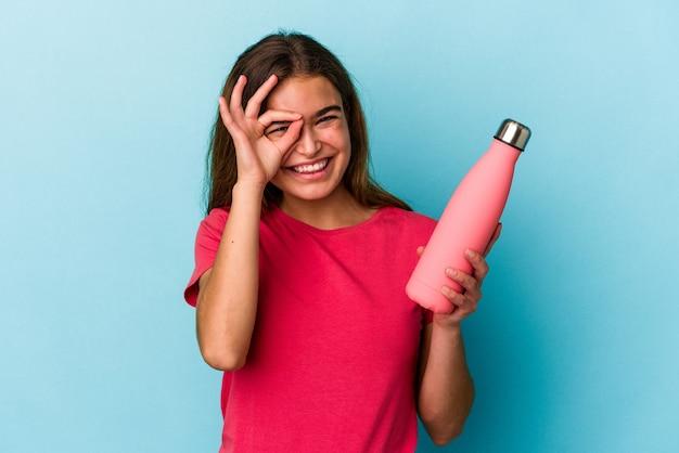 Junge kaukasische frau, die eine wasserflasche lokalisiert auf blauem hintergrund hält, aufgeregt, ok geste auf auge zu halten.