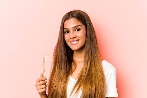 Junge kaukasische frau, die eine zahnbürste glücklich, lächelnd und fröhlich hält.
