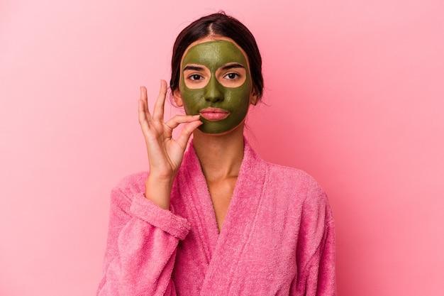 Junge kaukasische frau, die einen bademantel und eine gesichtsmaske trägt, die auf rosafarbenem hintergrund isoliert sind, mit den fingern auf den lippen, die ein geheimnis bewahren.