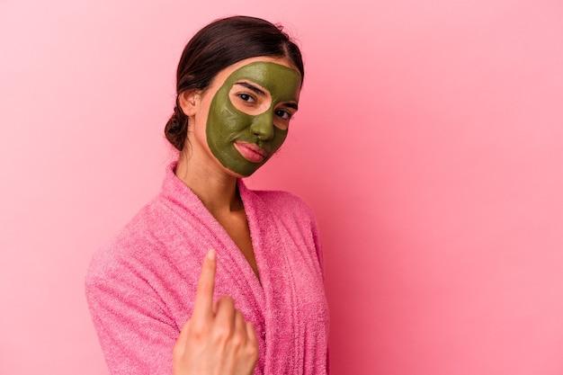 Junge kaukasische frau, die einen bademantel und eine gesichtsmaske trägt, einzeln auf rosafarbenem hintergrund, die mit dem finger auf sie zeigt, als ob sie einladen würde, näher zu kommen.