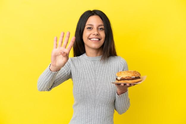 Junge kaukasische frau, die einen burger hält, der auf gelbem hintergrund glücklich ist und vier mit den fingern zählt