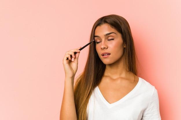 Junge kaukasische frau, die einen eyebrush getrennt anhält