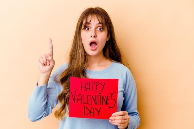 Junge kaukasische frau, die einen glücklichen valentinstag hält, lokalisiert mit einer großen idee, konzept der kreativität.