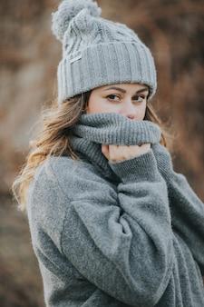 Junge kaukasische frau, die einen grauen pullover und eine wintermütze trägt