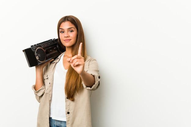 Junge kaukasische frau, die einen guetto-blaster hält, der nummer eins mit finger zeigt.