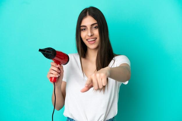 Junge kaukasische frau, die einen haartrockner einzeln auf blauem hintergrund hält, zeigt mit einem selbstbewussten ausdruck mit dem finger auf sie