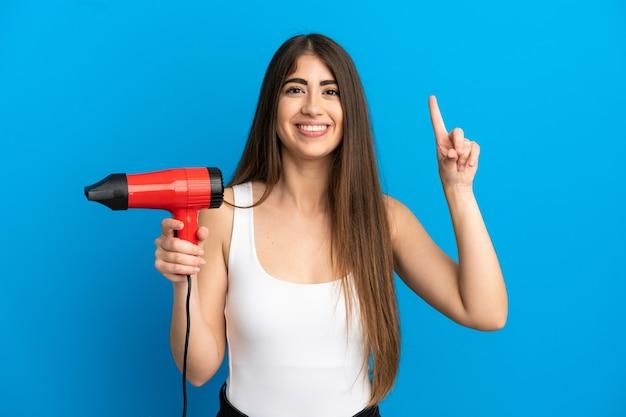 Junge kaukasische frau, die einen haartrockner isoliert auf blauem hintergrund hält und auf eine großartige idee zeigt
