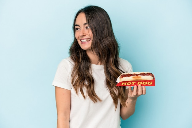 Junge kaukasische frau, die einen hot dog auf blauem hintergrund hält, sieht beiseite lächelnd, fröhlich und angenehm aus.