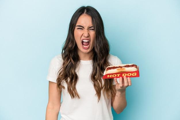 Junge kaukasische frau, die einen hot dog auf blauem hintergrund isoliert hält und sehr wütend und aggressiv schreit.