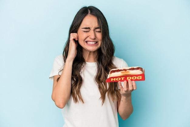 Junge kaukasische frau, die einen hot dog isoliert auf blauem hintergrund hält und die ohren mit den händen bedeckt.