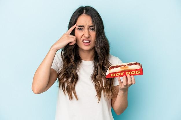 Junge kaukasische frau, die einen hotdog hält, der auf blauem hintergrund isoliert ist und eine enttäuschungsgeste mit dem zeigefinger zeigt.