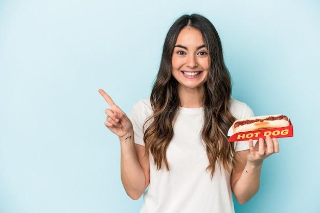 Junge kaukasische frau, die einen hotdog hält, der auf blauem hintergrund lokalisiert wird, lächelt und zeigt beiseite und zeigt etwas an der leerstelle.