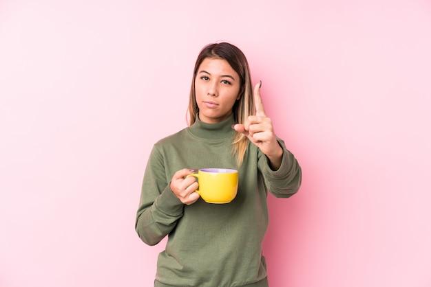 Junge kaukasische frau, die einen kaffee hält, der nummer eins mit finger zeigt.