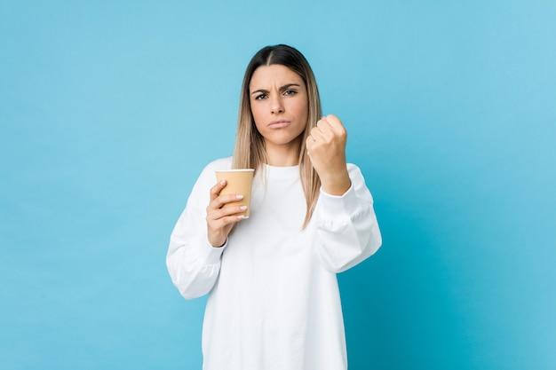 Junge kaukasische frau, die einen kaffee zum mitnehmen hält, der faust zur kamera, aggressiven gesichtsausdruck zeigt.