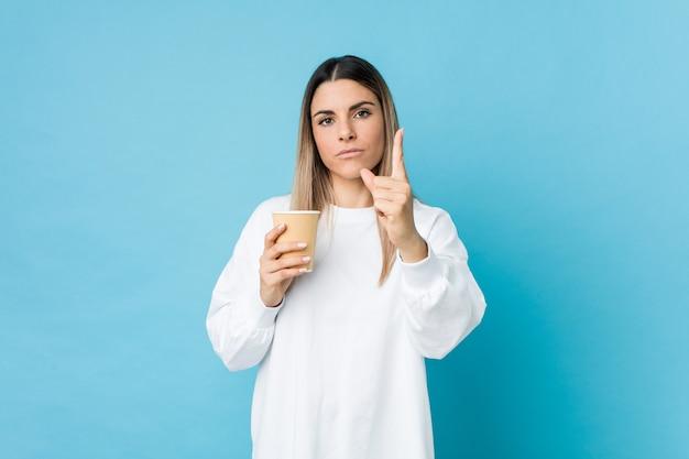 Junge kaukasische frau, die einen kaffee zum mitnehmen hält, der nummer eins mit finger zeigt.