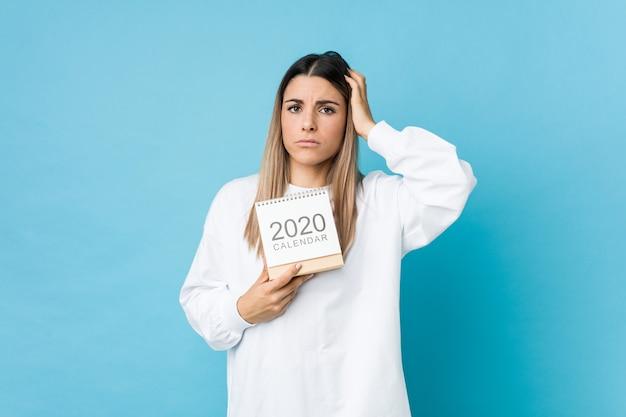 Junge kaukasische frau, die einen kalender 2020 hält, der schockiert ist, sie hat sich an wichtiges treffen erinnert.