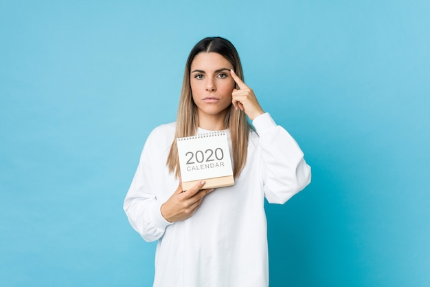 Junge kaukasische frau, die einen kalender 2020 hält, der seine schläfe mit dem finger zeigt und denkt, konzentrierte sich auf eine aufgabe.