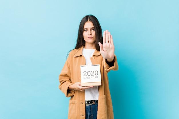 Junge kaukasische frau, die einen kalender 2020s steht mit der ausgestreckten hand zeigt das stoppschild und verhindert sie hält.