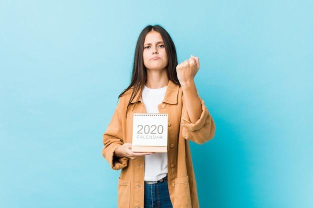 Junge kaukasische frau, die einen kalender 2020s zeigt faust zur kamera, aggressiver gesichtsausdruck hält.